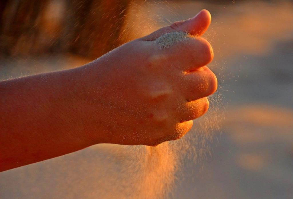 Sand rieselt durch Hand