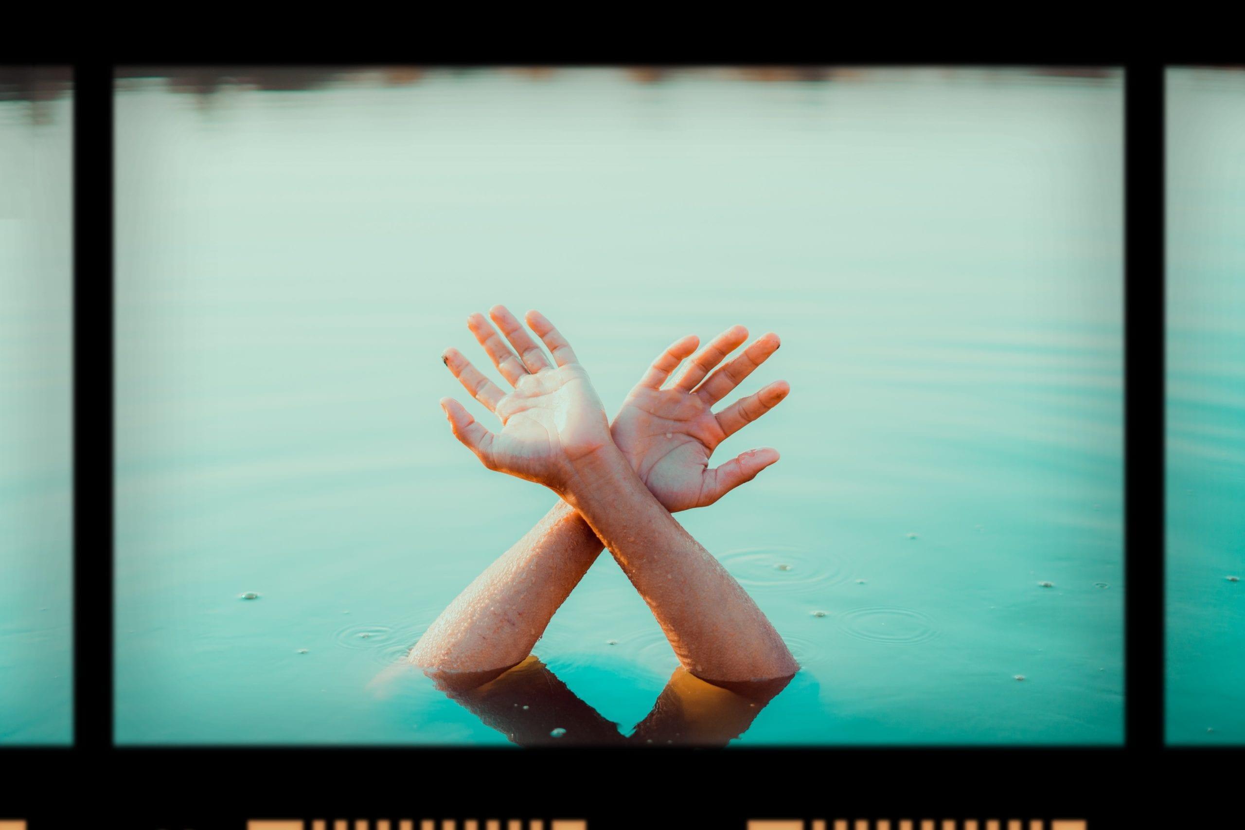 Mensch in milchigem Poolwasser streckt Hände nach oben