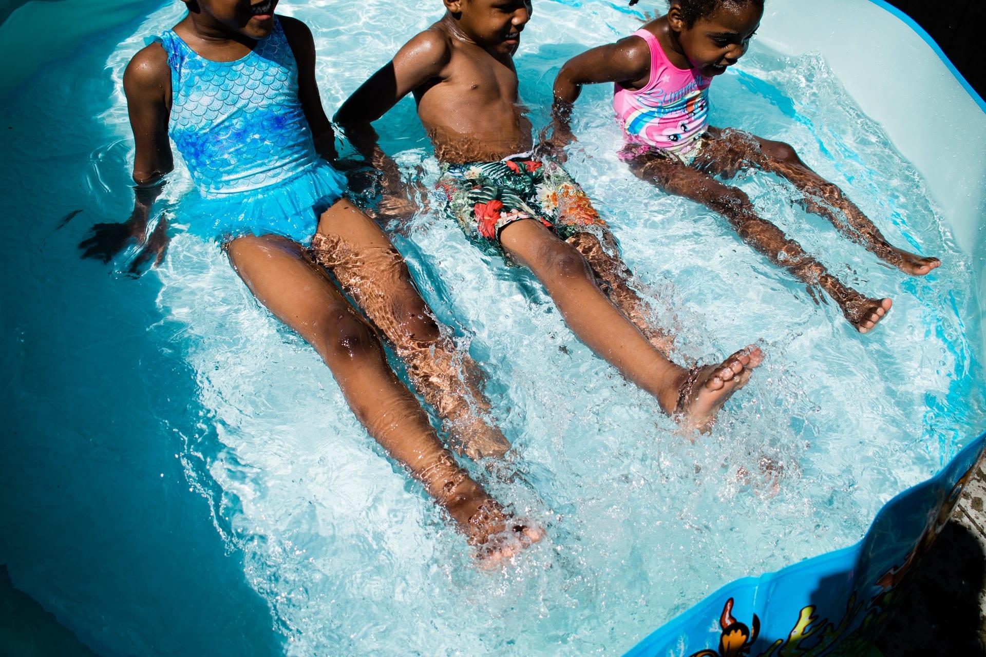 Planschbecken vor Entsorgung mit drei lachenden Kindern