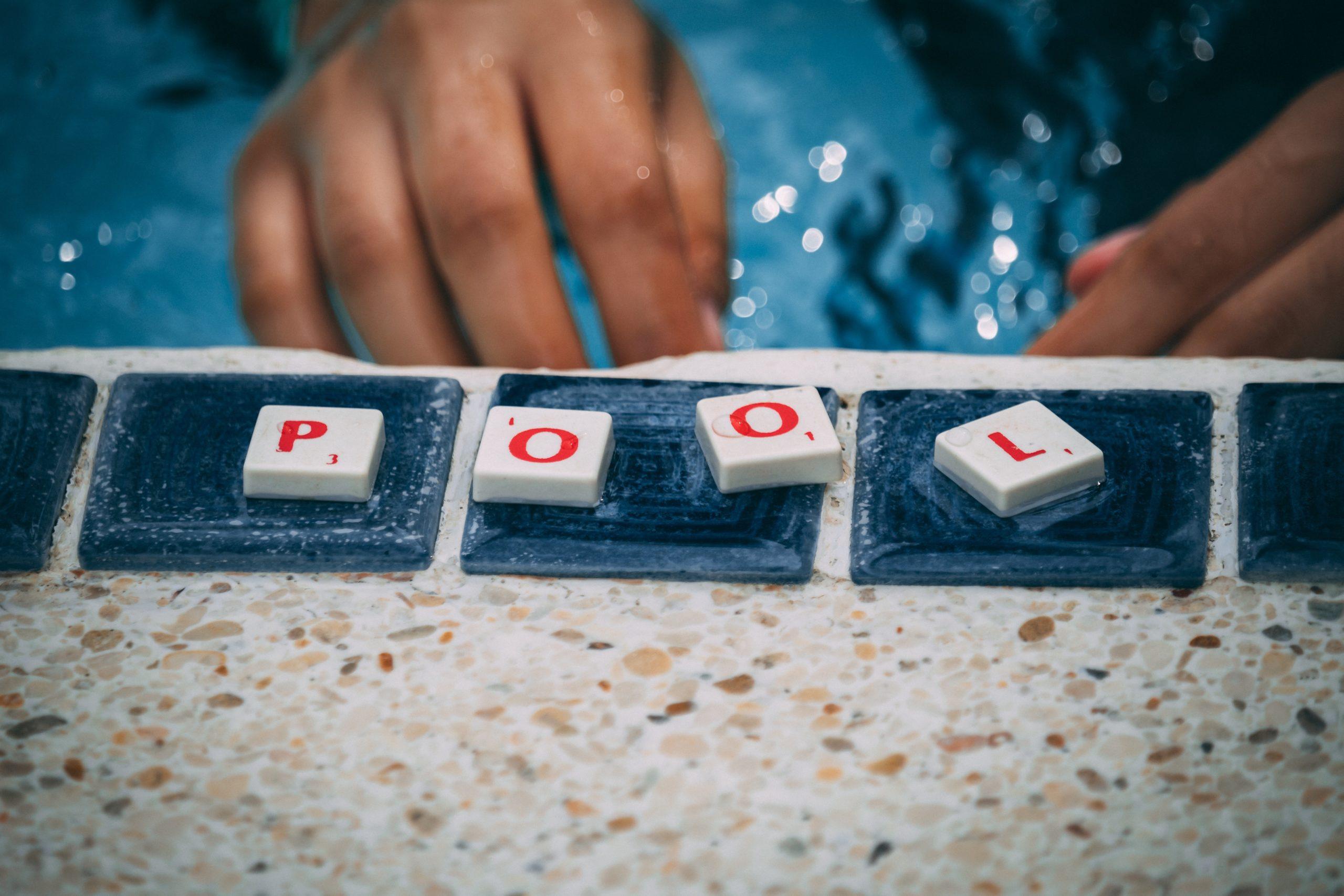 Das Wort Pool mit Scrabble Steinen am Beckenrand gelegt