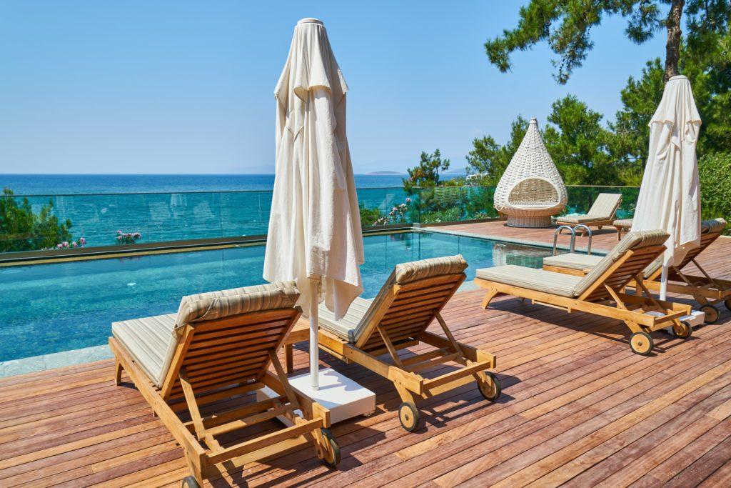 Poolbereich mit Poolliegen und Sonnenschirmen