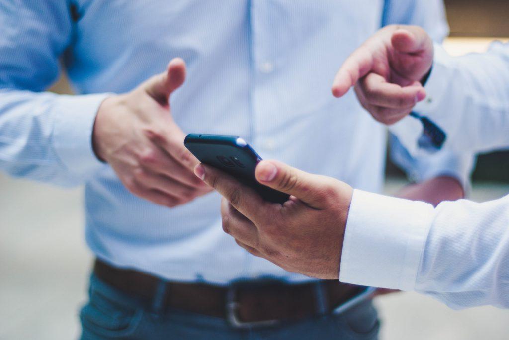 Mann zeigt auf sein Handy