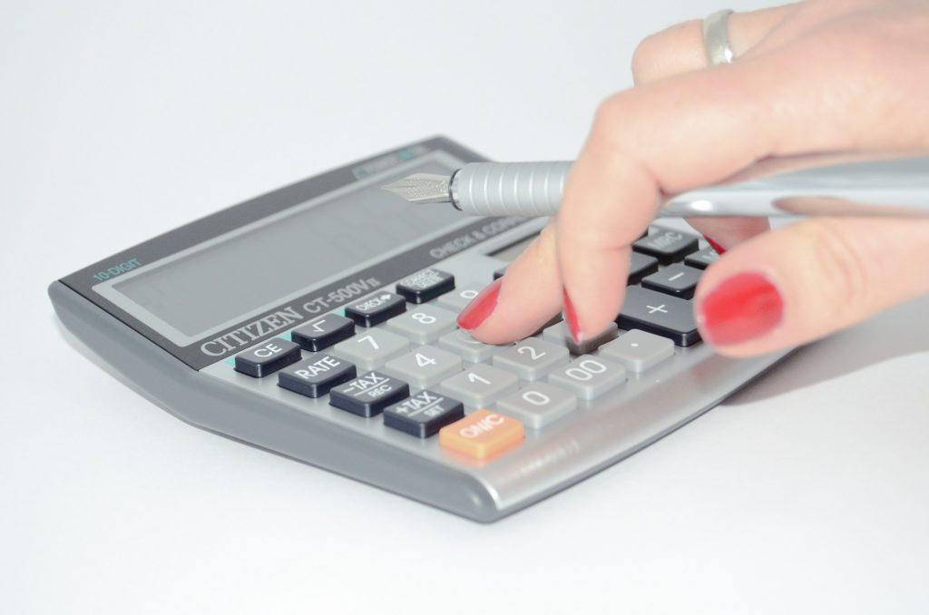 Taschenrechner wird von Frauenhänden bedient
